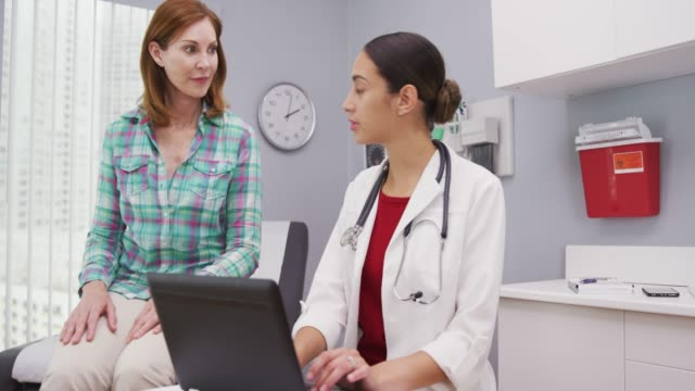 Young attractive latina doctor typing on laptop as she talks with senior patient