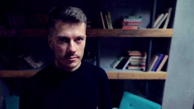 junger attraktiver mann im wohnzimmer - kopfbild stock-videos und b-roll-filmmaterial
