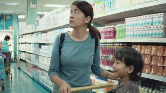 young attractive mom and little child buying food in a supermarket. - pushing stock videos & royalty-free footage