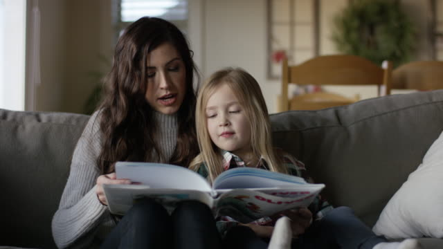 young attractive mother reading on the couch with her daughter - single mother stock videos & royalty-free footage