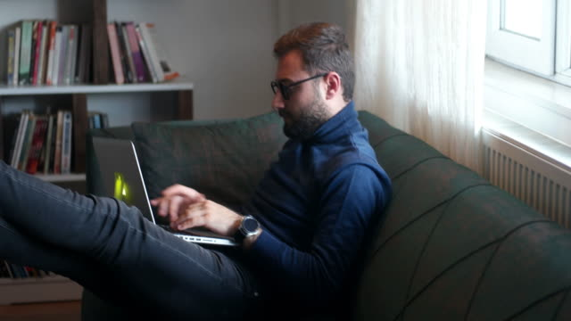 young attractive smiling guy is browsing at his laptop, sitting at home on the cozy green sofa at home, wearing casual outfit - post secondary education stock videos & royalty-free footage