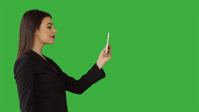 vídeos de stock, filmes e b-roll de young attractive white women using digital tablet computer browsing the web isolated on green screen chroma key background. female sales business professional - vestuário de trabalho formal