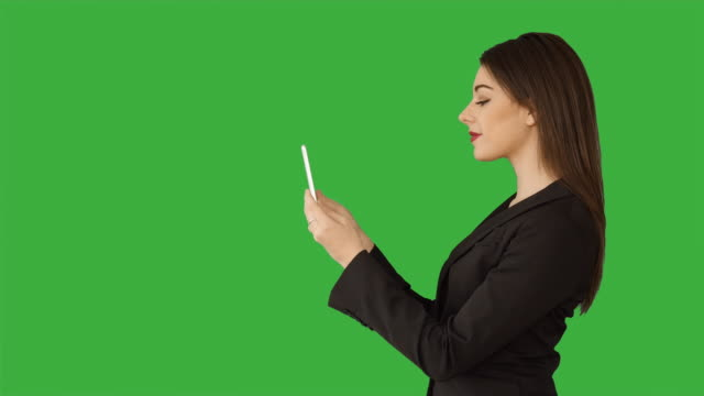 young attractive white women using digital tablet computer browsing the web isolated on green screen chroma key background. female sales business professional - profile stock videos and b-roll footage