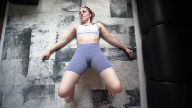 Young attractive woman doing home workout performing