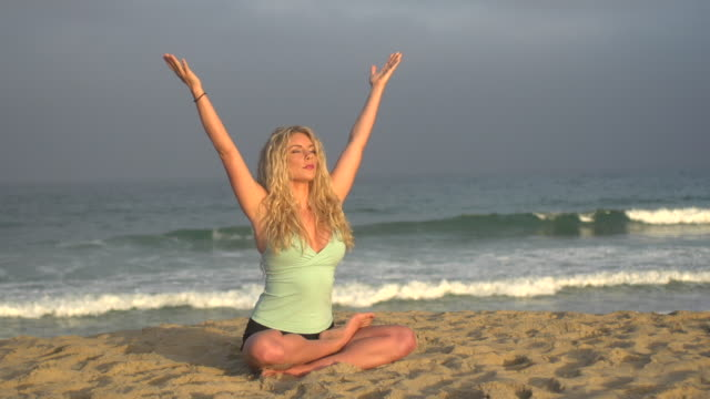 a young attractive woman doing yoga on the beach. - slow motion - seductive women stock videos & royalty-free footage