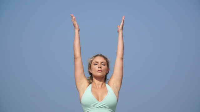 a young attractive woman doing yoga on the pier. - slow motion - brustbereich stock-videos und b-roll-filmmaterial