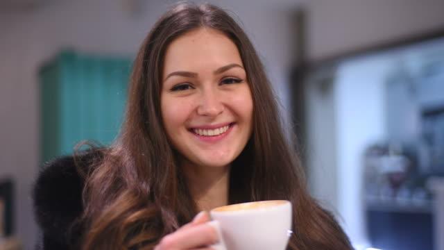 若い魅力的な女性のコーヒーを楽しみながら、カメラに笑いかけ - 毛皮のコート点の映像素材/bロール
