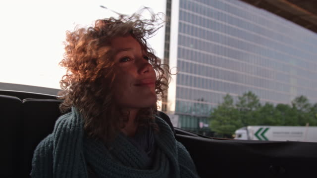 young attractive woman gets chauffeured through Munich in a cabriolet