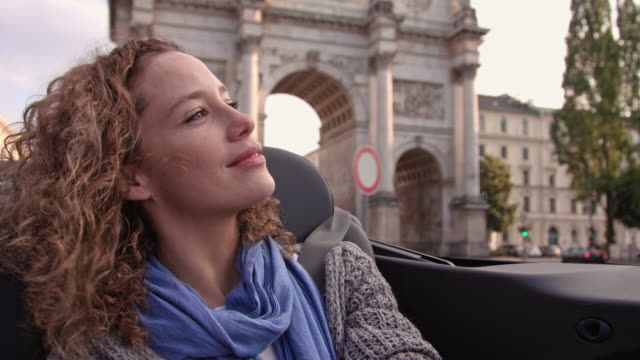 young attractive woman gets chauffeured through munich in a cabriolet - monumente stock-videos und b-roll-filmmaterial