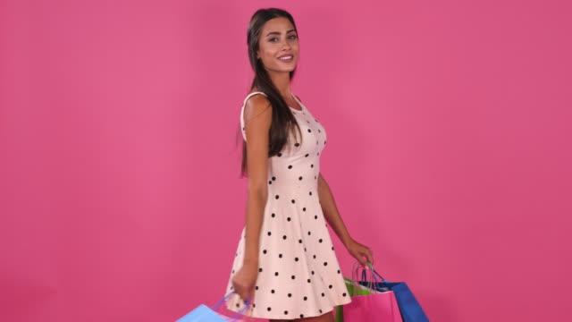 vidéos et rushes de jeune femme attirante regardant l'appareil-photo sur le fond rose, le mouvement lent - embarras du choix
