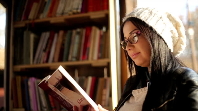 young attractive woman reading a book - book shop stock videos & royalty-free footage