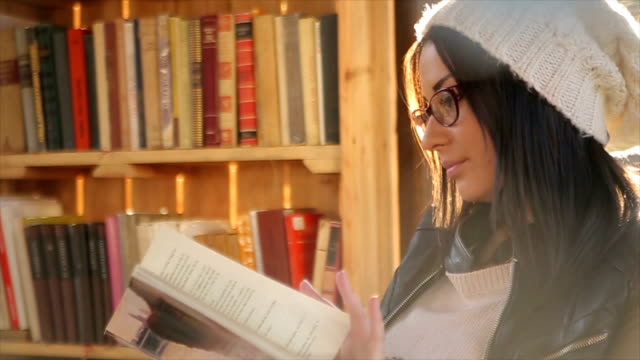 young attractive woman reading a book,and resting in the beautiful day - book shop stock videos & royalty-free footage