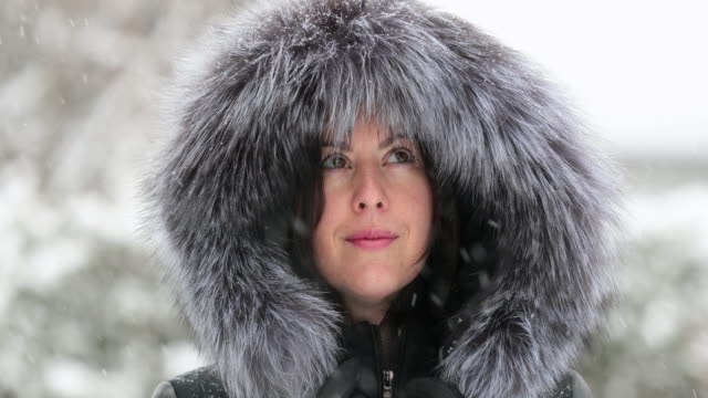 young attractive woman wearing fur coat during snowstorm - winter coat stock videos & royalty-free footage
