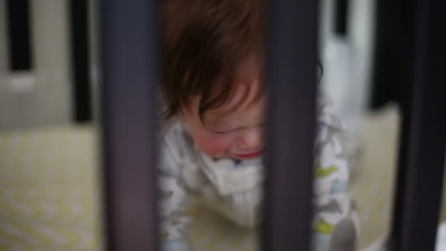 A young baby girl lying in her crib after waking up from a nap.