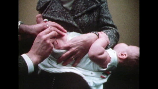 a young baby is vaccinated in the leg; 1982 - two generation family stock videos & royalty-free footage