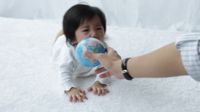MS young baby with  the world globe,trying to be pacified by rattle and globe/Singapore