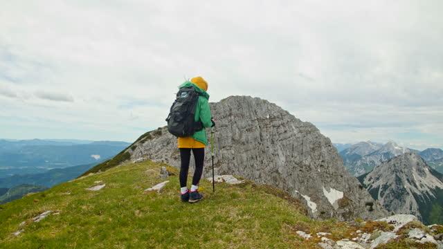 vídeos y material grabado en eventos de stock de slow motion mochilero joven caminando en la cima de la montaña usando bastones - artículo de montañismo