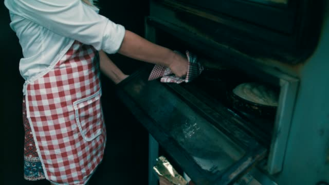 young baker takes out roasted meat pie from oven - oven mitt stock videos and b-roll footage