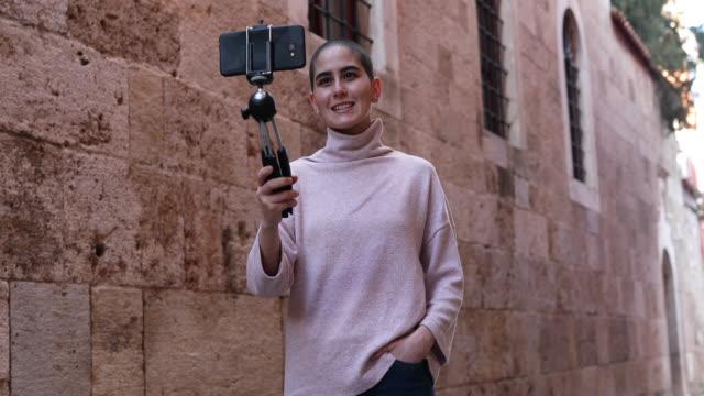 vidéos et rushes de jeune fille chauve prenant le vlog - blog vidéo