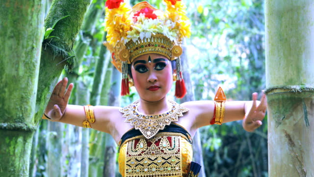 young balinese dancer performing barong dance in a bamboo forest - danza tradizionale video stock e b–roll