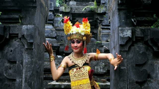vídeos de stock e filmes b-roll de young balinese dancer performing barong dance in a hindu temple - bali