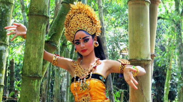 young balinese dancer performing legong dance in a bamboo forest - balinese culture stock videos & royalty-free footage