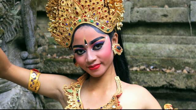 vídeos y material grabado en eventos de stock de bailarín balinés de jóvenes realizando danza legong en un templo hindú - bali