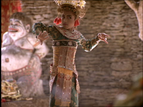Young Balinese girl in costume performing native dance / Indonesia