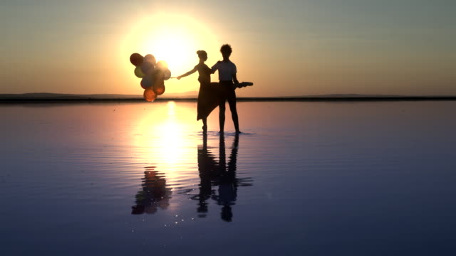 young ballerina and ballet dancing on the lake in the evening.