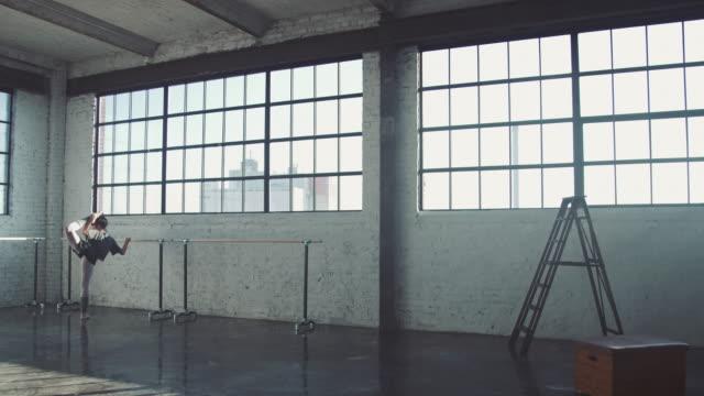 vídeos de stock e filmes b-roll de young ballerina dancing by barre in studio - bailarina de ballet