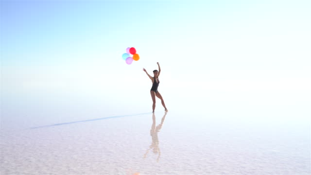 young ballerina dancing on the lake with color balloons - ballet dancer stock videos and b-roll footage