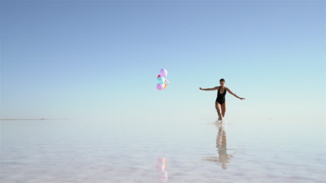 Young ballerina dancing on the lake with color balloons