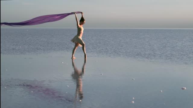 Jungen Ballerina tanzen auf dem Salzsee mit Farbe Tüll