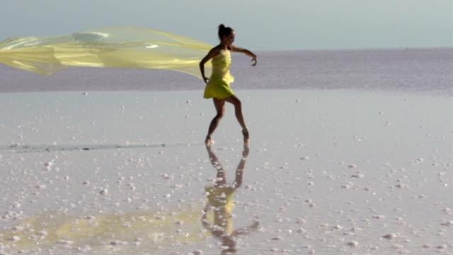 vídeos de stock, filmes e b-roll de jovem bailarina dançando sobre o lago de sal com tule cor - lago reflection