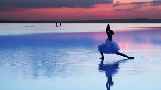 stockvideo's en b-roll-footage met jonge ballerina dansen op het water - sunshine lake