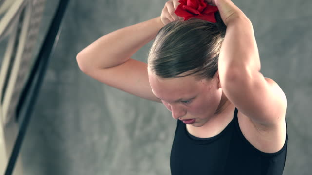 MS TD TU young ballerina girl sitting on floor pinning  red rose into her hair in preparation for  ballet performance / Rancho Mirage, California, United States