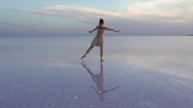 Young ballerina solo dancing on the salt lake
