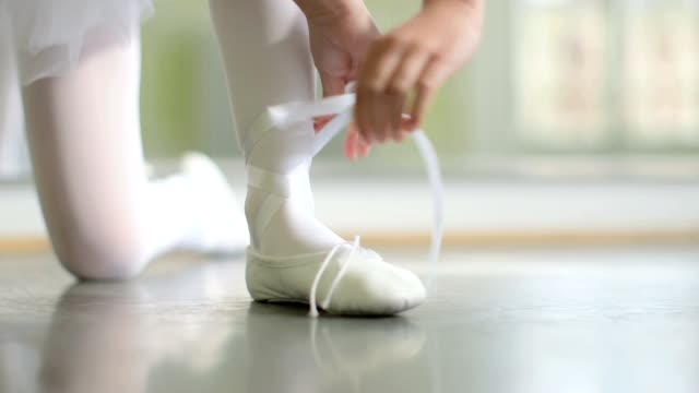 a young ballerina ties the ribbons of her soft top ballet shoes - ballet shoe stock videos & royalty-free footage