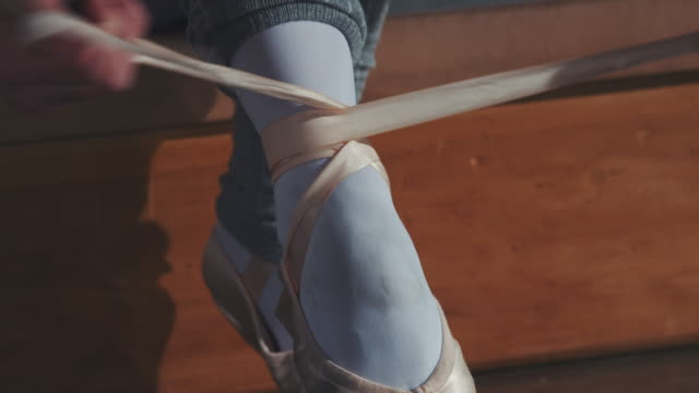 young ballerina tying her ballet shoe in studio - ballet shoe stock videos & royalty-free footage
