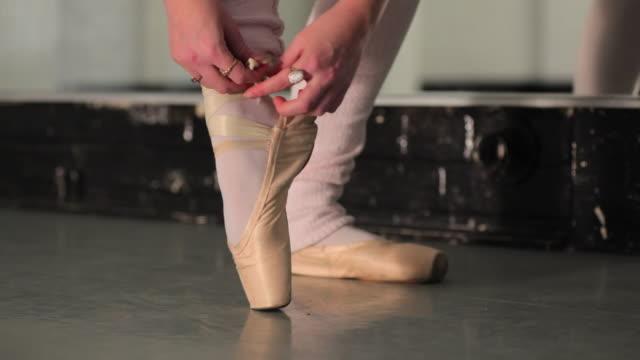vídeos y material grabado en eventos de stock de cu young ballerina tying pointe shoe ribbon / london, england - de puntas