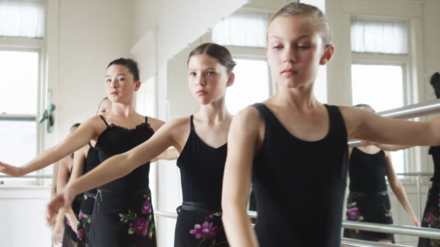 young ballerinas in a row - ballettstange stock-videos und b-roll-filmmaterial