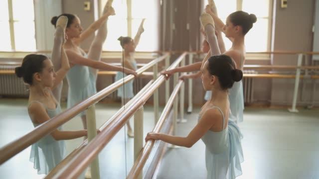 バールに伸びる若いバレリーナ - バレエ練習用バー点の映像素材/bロール