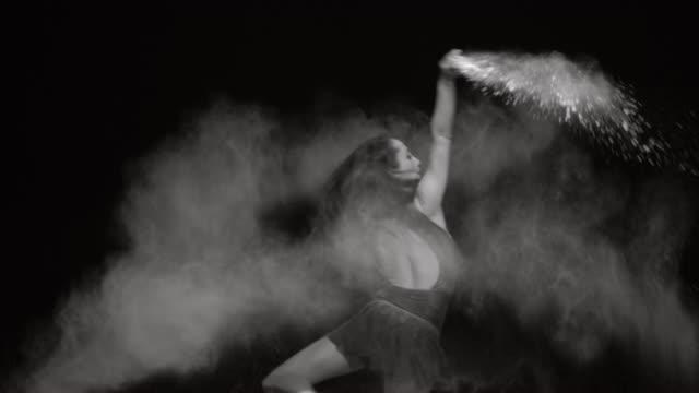 vídeos de stock, filmes e b-roll de jovem bailarina saltando em nuvem de pó branco - sapatilha de balé calçados esportivos