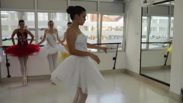 vídeos y material grabado en eventos de stock de niñas de ballet joven entrenando juntos en el estudio - malla de gimnasia