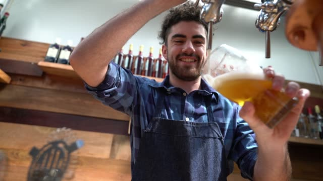 Young bar tender serving tap beer looking very happy and smiling