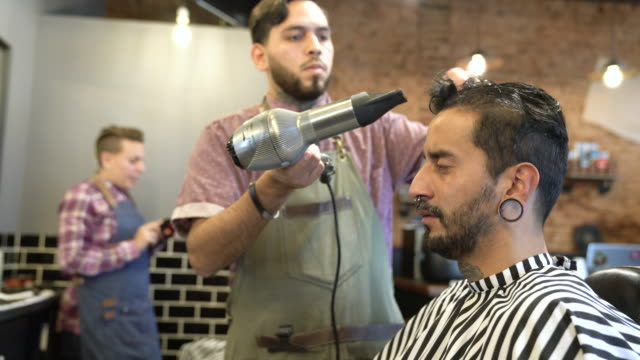 Young barber drying customer's hair in salon