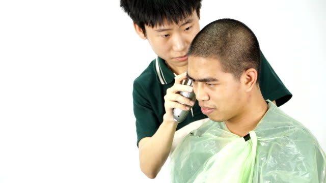 young barber making skinhead to Thai man