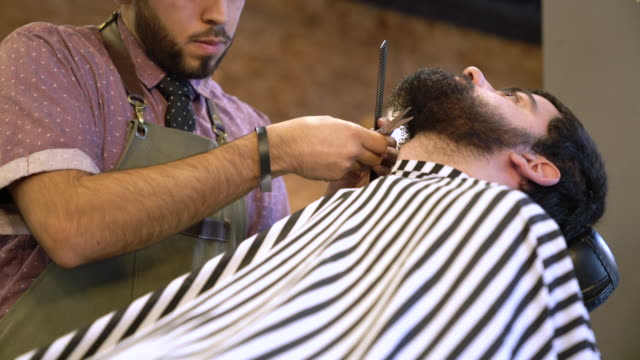 young barber trimming beard of client in salon - hair length stock videos and b-roll footage