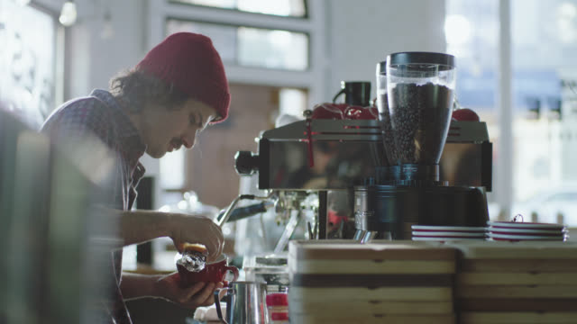 vidéos et rushes de ms. young barista mixes steamed milk and espresso in modern coffee shop. - chemise