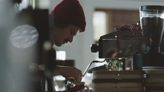 MS. Young barista mixes steamed milk and espresso to make latte in modern coffee shop.